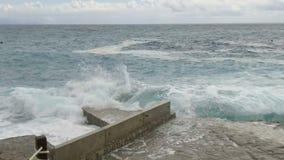 Rottura delle onde del mare sul pilastro di pietra Movimento lento archivi video