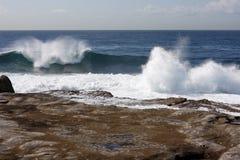 Rottura delle onde lungo il puntello roccioso Fotografia Stock