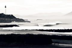 Rottura delle onde sotto un faro francese Immagini Stock