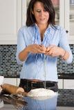 Rottura delle uova nella cucina fotografie stock
