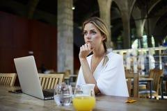 Rottura di presa femminile fra lavoro sul NET-libro durante la prima colazione Fotografia Stock