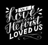 Rotulação da mão com verso que da Bíblia nós amamos porque nos amou primeiramente no fundo preto ilustração royalty free