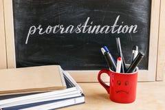 Rotulação da procrastinação da palavra no quadro preto em um backg fotos de stock