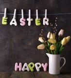 Rotulação das tulipas felizes da Páscoa e do ramalhete das cookies no fundo de pedra Fotografia de Stock Royalty Free