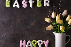 Rotulação das tulipas felizes da Páscoa e do ramalhete das cookies no fundo de pedra Fotos de Stock