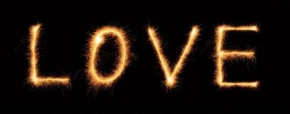 Rotulação do amor tirada com sparkles bengalis Fotografia de Stock Royalty Free