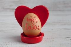 A rotulação 2017 feliz da Páscoa no ovo com coração vermelho deu forma ao suporte Imagens de Stock