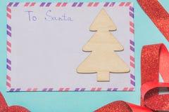 Rotule a Papai Noel uma letra da lista de objetivos pretendidos em um fundo azul Fotos de Stock Royalty Free