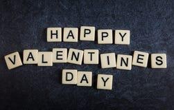 Rotule telhas no fundo preto da ardósia que soletra o dia de Valentim feliz foto de stock royalty free