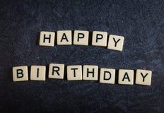 Rotule telhas no fundo preto da ardósia que soletra o feliz aniversario fotografia de stock royalty free