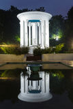 Rotunda and benches on pavement in light lantern at night Royalty Free Stock Images