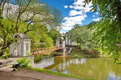 Rotunda on the shore of a pond in a city park. Sunny day. Reflection in water. Rotunda on the shore of a pond in a city park. Summer, sunny day. Reflection in royalty free stock images
