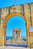Rotunda of Siege Bell War Memorial in the arch, Valletta, Malta. VALLETTA, MALTA - JUNE 17, 2018: The arched wall of Lower Barrakka Gardens opens the view of Stock Images