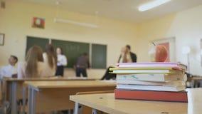 Rotura de la escuela en la sala de clase Los libros con la manzana están en la tabla Tema de la escuela almacen de metraje de vídeo