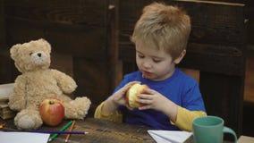 Rotura de la escuela Ni?o hambriento que come la manzana en sala de clase Niño pequeño en el escritorio delante de la pizarra que almacen de video