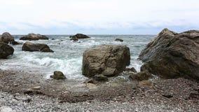 Rotura de las ondas del mar sobre piedras grandes almacen de metraje de vídeo