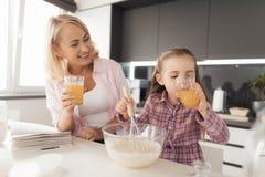Rotura en la preparación de la empanada Una muchacha y una mujer están bebiendo el jugo Fotografía de archivo libre de regalías