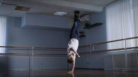 Rotura profesional el bailarín en el pasillo para los entrenamientos Él trabaja elementos difíciles, se prepara para el empleo co metrajes