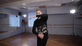 Rotura profesional el bailarín en el pasillo para los entrenamientos Él trabaja elementos difíciles, se prepara para el empleo co almacen de video