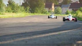 Roturación de los coches de carreras del Fórmula 1, tomando vuelta metrajes