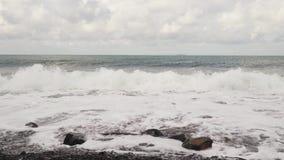 Roturas de la onda contra las rocas con el sonido almacen de video