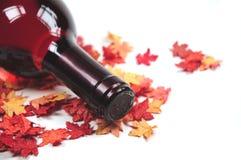 Rotwein auf Herbstblättern Stockfotografie
