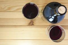 Rotwein auf Kiefernholz-Tabellenhintergrund Stockfotografie