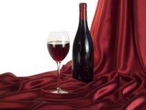 Rotwein auf rotem Satin Lizenzfreie Stockfotos
