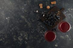 Rotwein in den Glasbechern mit Trauben auf einem dekorativen Brett Auf einem dunklen Hintergrund lizenzfreie stockbilder