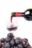 Rotwein, der in den Becher gießt Stockfotografie
