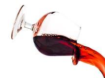Rotwein, der ein transparentes Glas überläuft Lizenzfreies Stockfoto