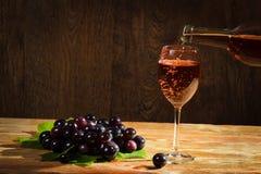Rotwein, der unten zum Glas mit Trauben gießt Stockfotos