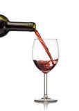 Rotwein, der in Weinglas gegossen wird Stockbilder