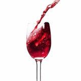 Rotwein des Spritzens in einem Glas. Stockbilder