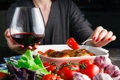 Rotwein des weiblichen Getränks und Essen von roiast Huhn lizenzfreies stockfoto