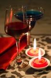 Rotwein glassl und blaues Cocktail mit roter Kerze Stockbild
