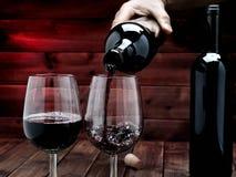 Rotwein goss aus einer Flasche in einem eleganten Kristallbecher, auf stockfoto