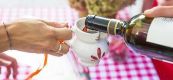 Rotwein goss in keramischen Krug Stockfotos