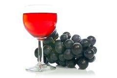 Rotwein im Glas mit Traube Stockbild