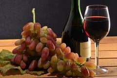 Rotwein und eine Weintraube Stockfotos