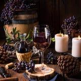 Rotwein von einem Fass mit Trauben und einem Glas Wein lizenzfreie stockfotos