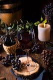 Rotwein von einem Fass mit Trauben und einem Glas Wein Stockfotografie