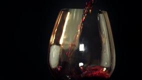 Rotwein wird in ein Glas gegossen stock video