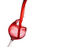Rotwein wird in ein Weinglas gegossen stockfotografie