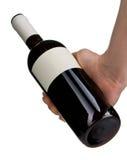 Rotweinflasche holded durch die lokalisierte Hand des Mannes Lizenzfreie Stockfotos