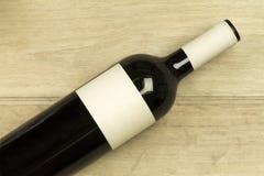 Rotweinflasche legt am hellen hölzernen Hintergrund nieder Stockfotografie