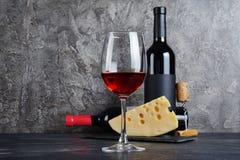 Rotweinflaschen mit Glas und Käse für das Schmecken im Keller lizenzfreie stockfotos
