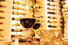 Rotweingläser auf einer hölzernen Planke mit defocused Flaschen beanspruchen im Hintergrund stark stockfotografie