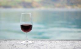 Rotweinglas auf Bar über Unschärfegrün-Seehintergrund Stockfotos