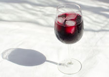 Rotweinglas mit Eis Stockbild
